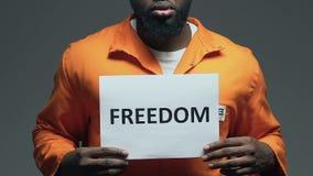 Palabra de la libertad en la cartulina en las manos del preso afroamericano, pidiendo amnistía metrajes