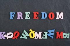 Palabra de la LIBERTAD en el fondo negro compuesto de letras de madera del ABC del bloque colorido del alfabeto, espacio del tabl Fotografía de archivo