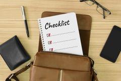 Palabra de la lista de control escrita en el cuaderno colocado dentro de un bolso de cuero del ` s de los hombres Foto de archivo libre de regalías