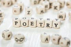 Palabra de la poesía escrita en el bloque de madera imagen de archivo