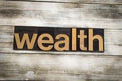 Palabra de la prensa de copiar de la riqueza en fondo de madera fotos de archivo
