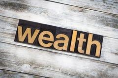 Palabra de la prensa de copiar de la riqueza en fondo de madera foto de archivo