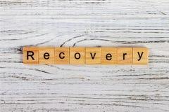 Palabra de la recuperación escrita en concepto de madera del cubo imagen de archivo