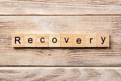 Palabra de la recuperación escrita en el bloque de madera texto en la tabla, concepto de la recuperación fotos de archivo libres de regalías