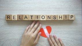 Palabra de la relación en los cubos de madera, manos femeninas que ponen el remiendo en el corazón de papel almacen de metraje de vídeo