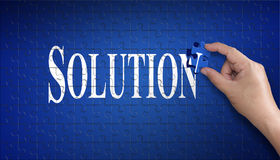 Palabra de la solución en rompecabezas Mano del hombre que lleva a cabo un rompecabezas azul t Foto de archivo