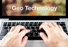 Palabra de la tecnología de Geo en la pantalla del cuaderno con el tipo de la mano en keyboar Foto de archivo libre de regalías