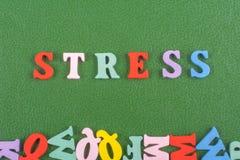 Palabra de la TENSIÓN en el fondo verde compuesto de letras de madera del ABC del bloque colorido del alfabeto, espacio de la cop Foto de archivo