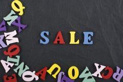Palabra de la venta en el fondo negro compuesto de letras de madera del ABC del bloque colorido del alfabeto, espacio del tablero Fotos de archivo libres de regalías