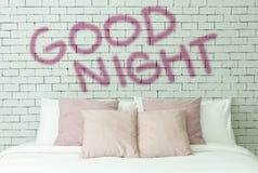Palabra de las buenas noches en el fondo blanco de pared de ladrillos Imagenes de archivo