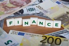 Palabra de las finanzas con las letras entre billetes de banco Imagenes de archivo