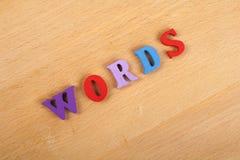 Palabra de las letras de las palabras en el fondo de madera compuesto de letras de madera del ABC del bloque colorido del alfabet Fotografía de archivo