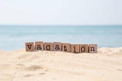 Palabra de las vacaciones en la playa soleada con el fondo del océano Imagenes de archivo