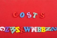 Palabra de los costes en el fondo rojo compuesto de letras de madera del ABC del bloque colorido del alfabeto, espacio de la copi fotografía de archivo