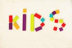 Palabra de los NIÑOS formados por los ladrillos coloridos del juguete imagenes de archivo