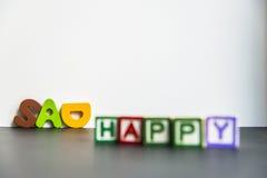 Palabra de madera colorida feliz y triste con background2 blanco Imagen de archivo libre de regalías