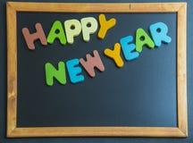 Palabra de madera de la Feliz Año Nuevo en tablero negro Imágenes de archivo libres de regalías