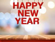 Palabra de madera roja de la Feliz Año Nuevo que cuelga sobre la sobremesa de madera con el bl Fotos de archivo