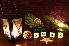 Palabra de Navidad con la vela de la linterna, la estrella, la rama del pino y la naranja Foto de archivo