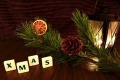 Palabra de Navidad con la vela de la linterna, la rama del pino y la naranja Fotografía de archivo