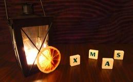 Palabra de Navidad con la vela y la naranja de la linterna Fotos de archivo