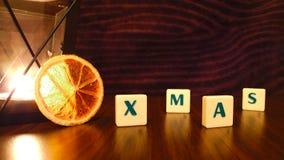 Palabra de Navidad con la vela y la naranja de la linterna Fotografía de archivo libre de regalías