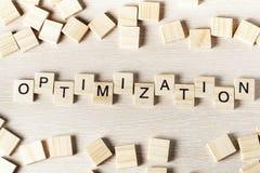 Palabra de Optinization escrita en el bloque de madera ABC de madera Imagen de archivo