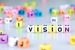 Palabra de Vision escrita en el cubo colorido con el bloque de palabra del cubo del bokeh foto de archivo