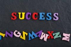Palabra del ÉXITO en el fondo negro compuesto de letras de madera del ABC del bloque colorido del alfabeto, espacio del tablero d Imágenes de archivo libres de regalías