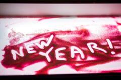 Palabra del ` del Año Nuevo del ` en la arena rosada Fotografía de archivo