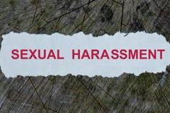 Palabra del acoso sexual en un periódico cortado fotos de archivo libres de regalías