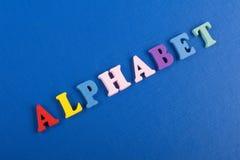 Palabra del ALFABETO en el fondo azul compuesto de letras de madera del ABC del bloque colorido del alfabeto, espacio de la copia Fotos de archivo