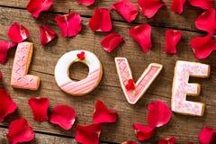 Palabra del amor con los pétalos rojos Fotografía de archivo