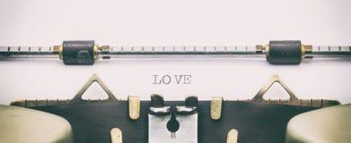 Palabra del AMOR con mayúsculas en una hoja de la máquina de escribir Foto de archivo