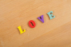 Palabra del AMOR en el fondo de madera compuesto de letras de madera del ABC del bloque colorido del alfabeto, espacio de la copi Fotos de archivo libres de regalías