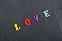 Palabra del AMOR en el fondo negro compuesto de letras de madera del ABC del bloque colorido del alfabeto, espacio del tablero de Fotografía de archivo libre de regalías