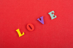 Palabra del AMOR en el fondo rojo compuesto de letras de madera del ABC del bloque colorido del alfabeto, espacio de la copia par Imágenes de archivo libres de regalías