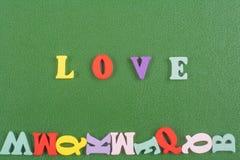 Palabra del AMOR en el fondo verde compuesto de letras de madera del ABC del bloque colorido del alfabeto, espacio de la copia pa Imagenes de archivo