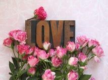 Palabra del amor en el tipo de madera con las rosas Fotos de archivo