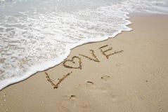 Palabra del amor encendido en la playa Imagen de archivo
