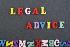 Palabra del ASESORAMIENTO JURÍDICO en el fondo negro compuesto de letras de madera del ABC del bloque colorido del alfabeto, espa Imágenes de archivo libres de regalías