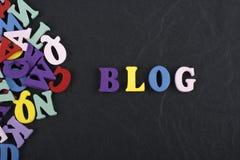 Palabra del BLOG en el fondo negro compuesto de letras de madera del ABC del bloque colorido del alfabeto, espacio del tablero de Imágenes de archivo libres de regalías
