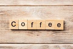 Palabra del café escrita en el bloque de madera texto en la tabla, concepto del café imagenes de archivo
