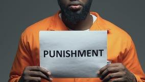 Palabra del castigo en la cartulina en las manos del preso afroamericano, pena de muerte almacen de metraje de vídeo