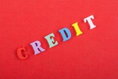 Palabra del CRÉDITO en el fondo rojo compuesto de letras de madera del ABC del bloque colorido del alfabeto, espacio de la copia  Fotografía de archivo libre de regalías