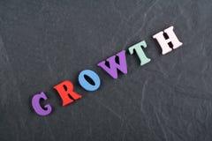 Palabra del crecimiento en el fondo negro compuesto de letras de madera del ABC del bloque colorido del alfabeto, espacio del tab Fotos de archivo libres de regalías
