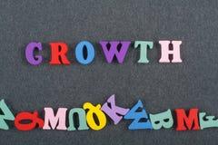 Palabra del crecimiento en el fondo negro compuesto de letras de madera del ABC del bloque colorido del alfabeto, espacio del tab Imagen de archivo