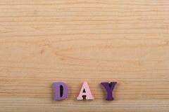 Palabra del DÍA en el fondo de madera compuesto de letras de madera del ABC del bloque colorido del alfabeto, espacio de la copia Fotografía de archivo libre de regalías