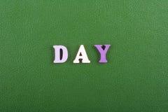 Palabra del DÍA en el fondo verde compuesto de letras de madera del ABC del bloque colorido del alfabeto, espacio de la copia par Imágenes de archivo libres de regalías