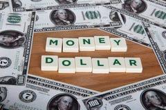 Palabra del dólar del dinero con las letras entre billetes de banco Fotos de archivo libres de regalías